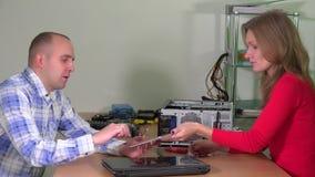 Teknikerkvinnan lyssnar till klientmanklagomål om den brutna bärbar datordatoren arkivfilmer