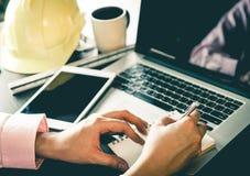 Teknikerleverantör som arbetar på bärbara datorn och anteckningsboken Arkivfoto