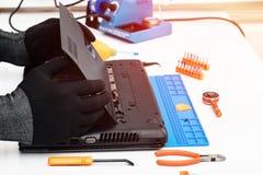 Teknikern demonterar detaljerna av en bruten b?rbar dator f?r reparation royaltyfri fotografi