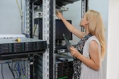 Teknikern It för den unga kvinnan med minnestavlan mellan serveren racks royaltyfri foto