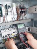 Teknikern gör underhåll av maktnätverksautomation Arkivbild