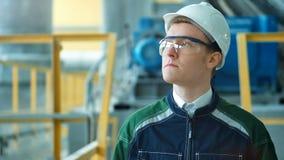 Teknikern i hardhat går i fabrik för tung bransch lager videofilmer