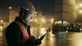 Teknikern i hardhat med en minnestavladator ser lastbilen på fabrik för tung bransch stock video