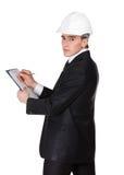 Teknikern i hård hatt gör anmärkningar Arkivfoton