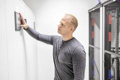 Teknikern justerar luftkonditioneringsapparaten i datacenter Arkivfoto