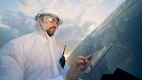 Teknikern kontrollerar solpaneler och skriver på en minnestavla Innovativt branschbegrepp stock video