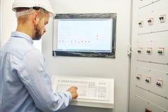 Teknikern kontrollerar teknologisk utrustning från fjärrkontrollbräde Scada system för automationutrustning royaltyfri foto