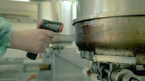 Teknikern med laser-termometervapnet mäter temperaturen av maskinen arkivfilmer