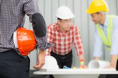 Teknikern och konstruktion team den bärande säkerhetshjälmen och seritningen på tabellen royaltyfri fotografi