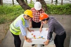 Teknikern och konstruktion team den bärande säkerhetshjälmen och seritningen på tabellen på konstruktionsplatsen arkivfoto
