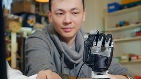 Teknikern på modernt startar upp kontoret att arbeta med den innovativa bioniska robotic armen Dockakamerarörelse arkivfilmer
