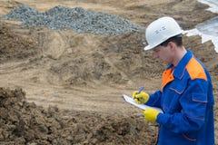 Teknikern planlägger förberedelsen av jorden för konstruktion av fundamentet och skriver i minnestavlan royaltyfri bild