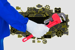 Teknikern rymmer ett arbetshjälpmedel mot mekanikerbakgrund Royaltyfria Bilder
