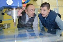 Teknikern Showing Apprentice How som ska anv?ndas, borrar in fabriken arkivfoton