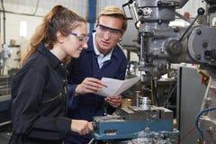 Teknikern Showing Apprentice How som ska användas, borrar in fabriken Arkivfoto