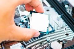 Teknikern som installerar centralenhetCPU på moderkortdatoren i datorlabb royaltyfri fotografi
