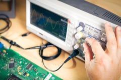 Teknikern testar elektroniska delar med oscilloskopet i den tjänste- mitten Arkivfoton