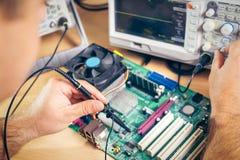 Teknikern testar elektroniska delar med oscilloskopet i den tjänste- mitten Royaltyfri Foto