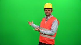 Teknikern Worker Making Presentation gör en gest på den gröna skärmen Uppvisning av den tillbaka sidan lager videofilmer