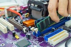 Teknikers händer som installerar RAM Arkivbild