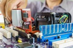 Teknikers händer som installerar VGA kortet Royaltyfri Bild