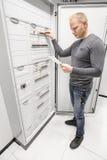 Teknikerströmbrytaresäkringen och läser tekniskt papper Royaltyfri Bild
