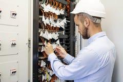Teknikerteknikern förbinder optiska fibrer in i kommunikationsströmbrytaren i datorhall Serviceman i datacenter royaltyfri fotografi