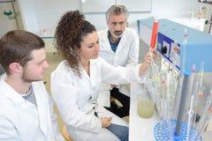 Teknikstudenter som använder den innovativa skrivaren 3d i laboratorium arkivbilder