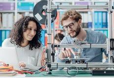 Teknikstudenter som använder en skrivare 3D arkivbilder