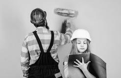 Teknikutbildning byggnadsarbetareassistent faderskap man med lilla flickan familj Bransch hj?lpmedel f?r arkivfoton