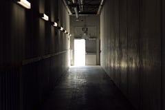 Teknisk korridor med ljus på slutet utgångstecken ovanför dörren royaltyfri fotografi