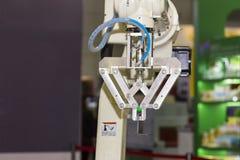 Tekniskt avancerad och precisionrobotarm med fattandet för låsprodukt i tillverkningsprocess arkivfoto