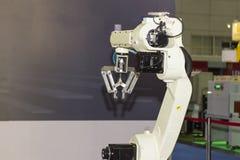Tekniskt avancerad och precisionrobotarm med fattandet för låsprodukt i tillverkningsprocess arkivbild