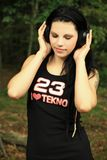 Tekno girl. Brunette in a black shirt tekno 23 in the woods has headphones on your ears and listens tekno Royalty Free Stock Photo