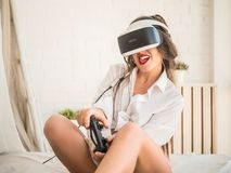 Teknologi-, dobbel-, underhållning- och folkbegrepp - ung kvinna med virtuell verklighethörlurar med mikrofon, kontrollantgamepad Royaltyfria Foton