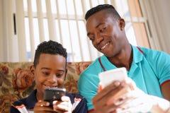 Teknologi för svart manundervisningmobiltelefon till pojken hemma Arkivfoto
