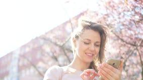 Teknologi i v?rt liv Stående av en härlig ung kvinna med en smartphone i hennes händer stock video