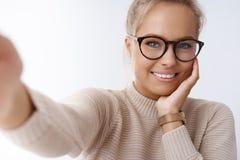 Teknologi-, mjukhet- och skönhetbegrepp Den mjuka snygga flickvännen som tar selfie som rymmer kameran, fördjupa handen royaltyfria foton