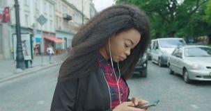 Teknologi och folk Mobilt beroende Den attraktiva unga afrikanska flickan korsar vägen och smsa som bläddrar via arkivfilmer