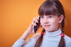 Teknologi och kommunikation, Caucasian tonårig flicka som talar på telefonen på en kulör bakgrund, ställe för text fotografering för bildbyråer