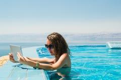 Teknologi- och semesterbegrepp Lyxigt lopp Ung nätt kvinna som använder minnestavladatoren i oändlighetspöl på semesterorten royaltyfri foto