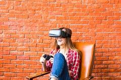 Teknologi-, virtuell verklighet-, underhållning- och folkbegrepp - kvinna med vrhörlurar med mikrofon som spelar leken Arkivfoton