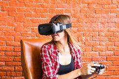 Teknologi-, virtuell verklighet-, underhållning- och folkbegrepp - kvinna med vrhörlurar med mikrofon som spelar leken Royaltyfri Fotografi
