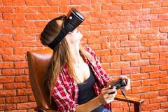 Teknologi-, virtuell verklighet-, underhållning- och folkbegrepp - kvinna med vrhörlurar med mikrofon som spelar leken Arkivfoto