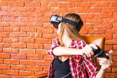 Teknologi-, virtuell verklighet-, underhållning- och folkbegrepp - kvinna med vrhörlurar med mikrofon som spelar leken Royaltyfri Foto