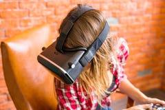Teknologi-, virtuell verklighet-, underhållning- och folkbegrepp - kvinna med vrhörlurar med mikrofon som spelar leken Royaltyfri Bild