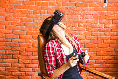 Teknologi-, virtuell verklighet-, underhållning- och folkbegrepp - kvinna med vrhörlurar med mikrofon som spelar leken Arkivbild