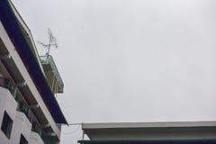 Teknologikommunikationstorn, TVantenn med den satellit- maträtten på bakgrund för blå himmel royaltyfri bild