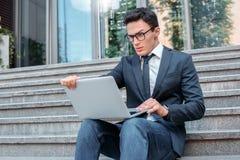 Teknologiproblem Affärsman i glasögon som sitter på trappa på stadsgatan som ser den förvirrade bärbar datorskärmen arkivbild