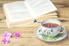 Tekopp, boken och blommor på trätabellen Royaltyfria Bilder